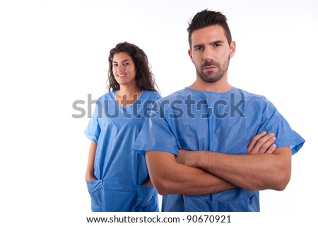 two doctors, a female and a male in blue uniforms looking confident and happy - stock photo