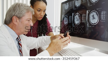 Two doctors analyzing brain xrays on computer - stock photo