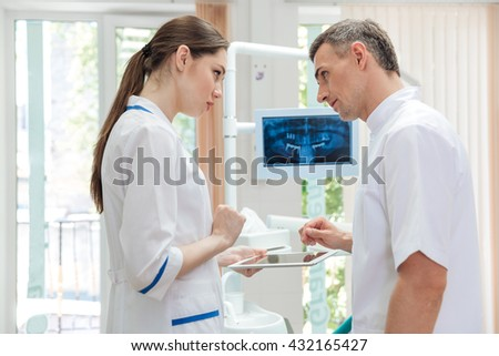 Two doctors dentists looking panoramic photo of teeth on the monitor in clinic - stock photo