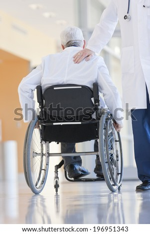 Two doctors, one in a wheelchair, walking in a hospital corridor. - stock photo
