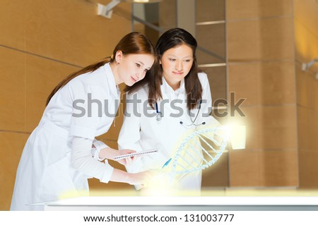 two doctors stand near glowing table discussing. projected objects on a desk - stock photo