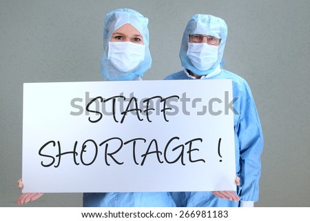 Two Doctors with shield staff shortage - stock photo