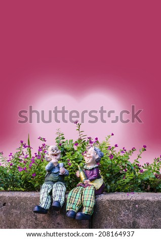 Two dolls which made like grand mom & grand dad sit on a brick wall in front of flowers and red heart back ground - stock photo