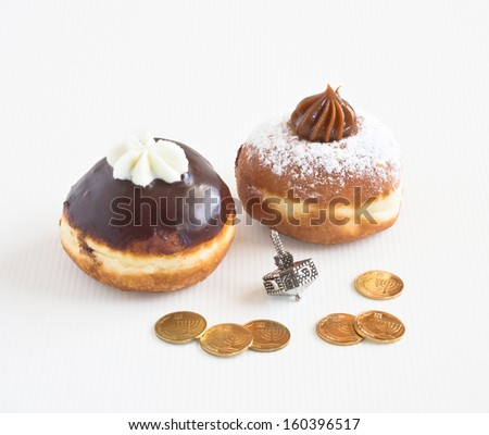 Two donuts with dreidel and coins during the Jewish holiday of Hanuka isolated on white background. - stock photo