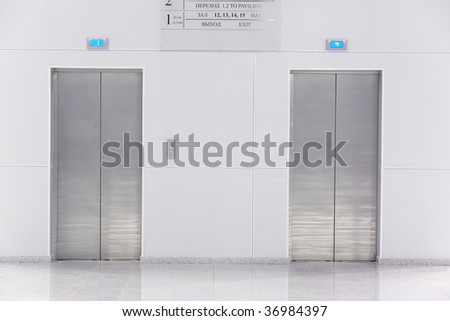 Two doors of elevators in modern business building - stock photo