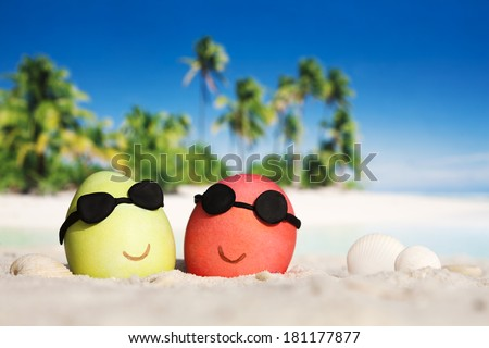 Two easter eggs with sunglasses on ocean beach  - stock photo
