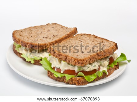 two egg salad sandwiches on brown toasted bread - stock photo