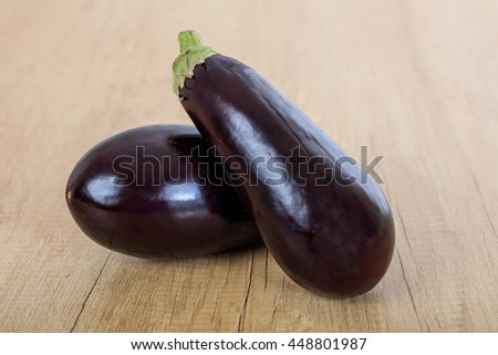 Two eggplants on a wooden surface - stock photo