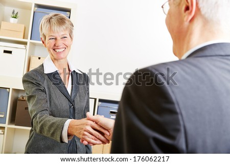 Two elderly business people greeting with a handshake at job interview - stock photo