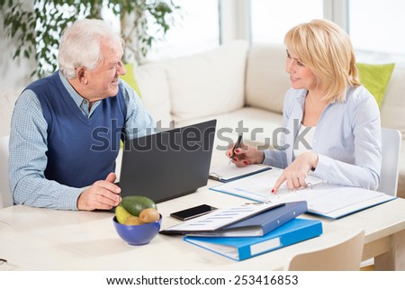 Two elderly businesspeople filling in the documents - stock photo