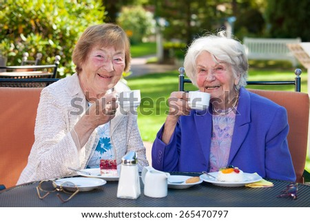Two Elderly Female Best Friends Sitting at the Outdoor Table While Holding Cups of Coffee and Smiling at the Camera. - stock photo