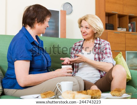 Two elderly females sitting on sofa and gossiping in home tea-drinking - stock photo