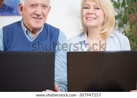 Two elderly happy businesspeople sitting with computers - stock photo