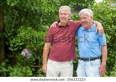 Two elderly men are embracing each other, looking to the left and are having a good time - stock photo