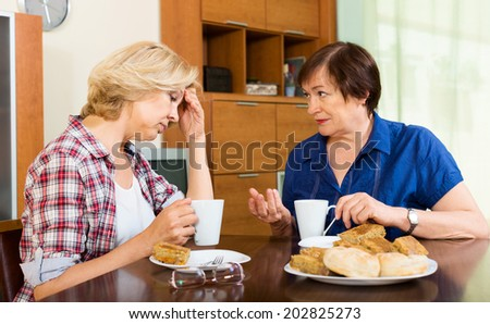 Two elderly woman with cup of tea discussing something at home - stock photo
