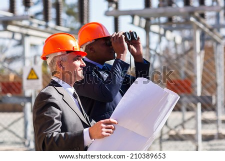two electrical managers with binoculars visiting power plant - stock photo