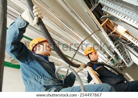 two electrician builder engineers workers installing industrial cable into fuse box - stock photo