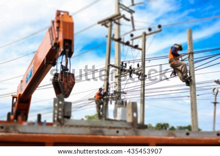 Two electrician repair electric transformers with crane truck blur. - stock photo