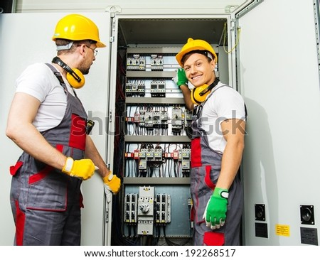 Two electricians in a safety hat and headphones on a factory - stock photo