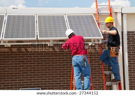Two electricians installing solar panels on a building. - stock photo