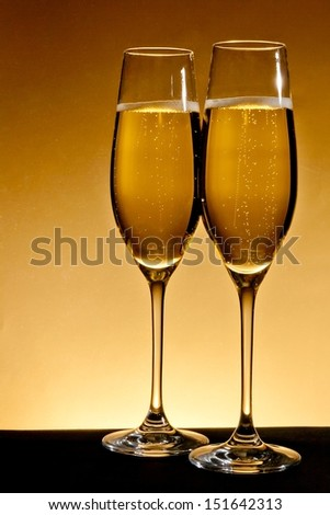 two elegant champagne glasses on golden background - stock photo