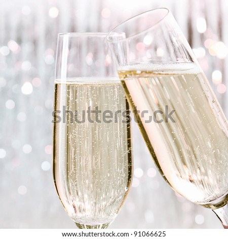 Two elegant flutes of sparkling white champagne with lots of bubbles on festive background, celebration concept. - stock photo