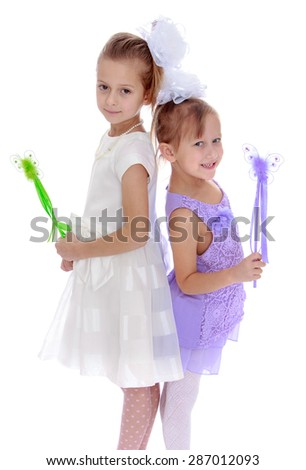 Two elegant little girls in beautiful dresses holding a magic wand-Isolated on white background - stock photo