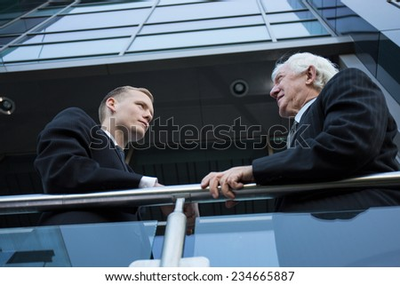 Two elegant men in suits conversing outside on the balcony - stock photo