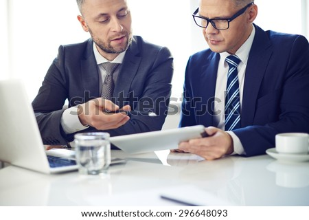 Two elegant men using digital tablet at meeting - stock photo