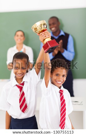 two elementary students holding a trophy in classroom - stock photo