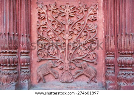 Two elephant under a tree of life. Bas-relief on the wall of an ancient temple in Rajasthan, India. - stock photo