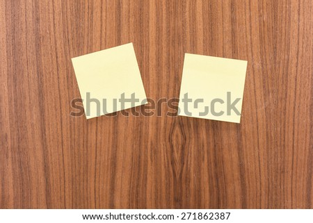 Two empty sticky notes on a wooden table. Conceptual image of office communication, message or reminder. - stock photo