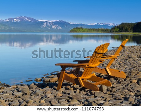 Two empty wooden Adirondack chairs or Muskoka deckchairs on stony shore overlooking scenic calm Lake Laberge, Yukon Territory, Canada, with snowcapped mountains in the distance - stock photo