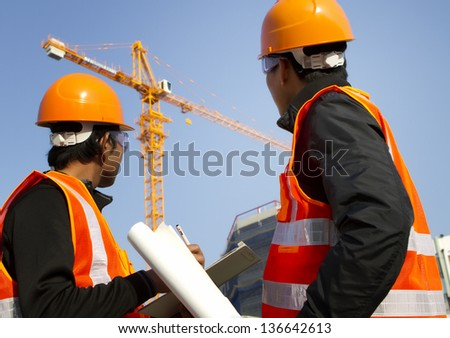 Two engineer construction. Site manager with safety vest discussion under construction - stock photo