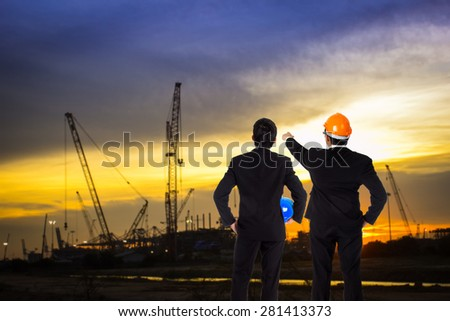 Two Engineer discussing about construction site progress in twilight time. - stock photo