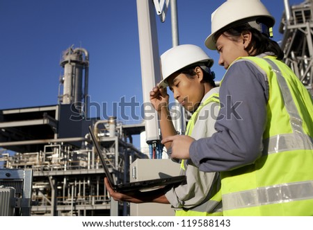 two engineer power and energy discussion on location site using laptop - stock photo