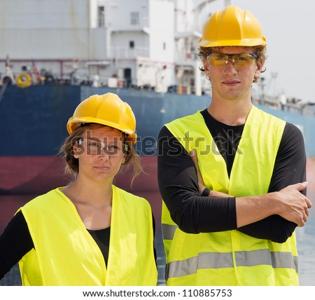 Two Engineering students posing in front of a huge freight vessel during their technological internship in a harbor - stock photo
