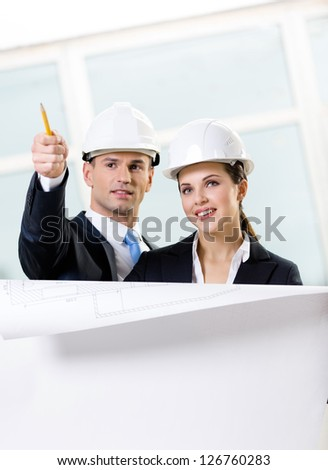 Two engineers discuss their cooperation keeping layout - stock photo