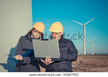 Two Engineers in Wind Turbine Power Generator Station - stock photo
