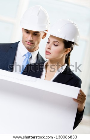 Two engineers looking at the sketch and discuss their cooperation - stock photo