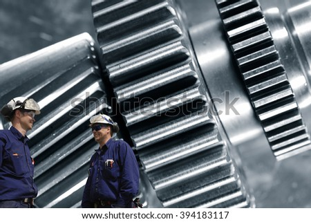 two engineers, mechanics with large cogwheels and gears machinery in background - stock photo