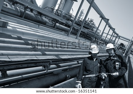 two engineers walking alongside large pipeline construction inside oil-refinery, blue toning idea - stock photo