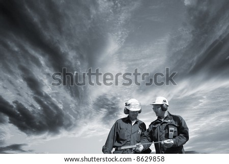 two engineers walking under a dark stormy sky, conceptual idea in a dark toning concept - stock photo