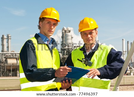 Two engineers, wearing reflective clothing and a hard hat, looking up from the note board they have been discussing - stock photo