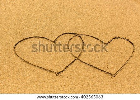 Two entangled hearts drawn out on a sandy beach. - stock photo