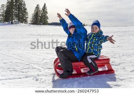 Two enthusiastic boys sledding. - stock photo