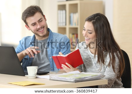 Two entrepreneurs working and taking notes together in table of a little office - stock photo