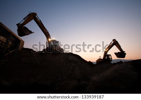 two escavators working on a mine at dawn - stock photo