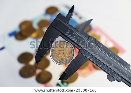 Two Euro coin being held by a vernier tool. Out-of-focus currency behind - stock photo