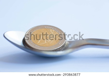 Two Euro coin in a tablespoon, as a symbol of a living wage - stock photo